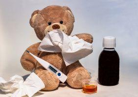 Teddybeer met thermometer en hoestsiroop