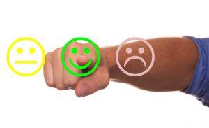 drie smileys (blij, gewoon, verdrietig) en vinger die erop duwt