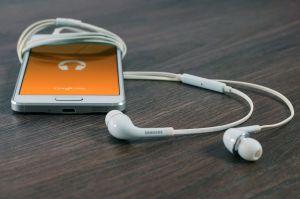 smartphone met oortjes ingeplugd