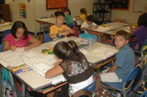 vier kinderen rond tafel in klas