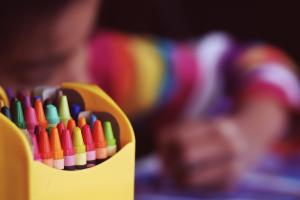 doosje met wasco's op de voorgrond, op de achtergrond staat een kind dat kleurt