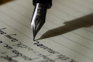 vulpen schrijft letters op een lijntjesblad