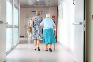 oude mensen wandelen door een gang