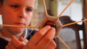 Kind maakt een spinnenweb met touw en een kastanje