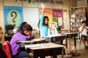 leerlingen in klas, 1 leerling steekt vinger op