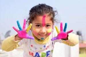 Kleuter met handen vol kleurrijke verf
