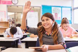 Enthousiast meisje dat hand opsteeks in de klas