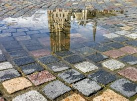 Sint-Rombout tower reflected in puddle of water