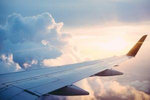 vleugel van een vliegtuig met op de achtergrond de zon