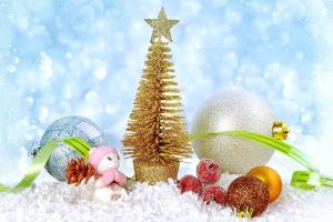 gouden kerstboompje waar sneeuwmannetjes en kerstballen naast liggen