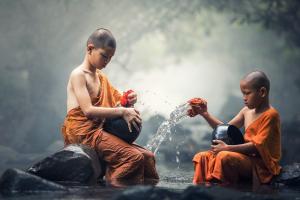 twee boeddhistische jongens zitten in een rivier op de rotsen