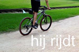 man op fiets en titel: hij rijdt