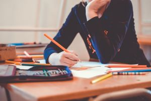 Leerling zit aan zijn bank met potlood in de hand