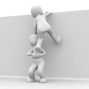 mannetje helpt mannetje over de muur