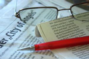 Krant, balpen en bril