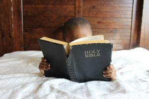 jongetje lezend in bed