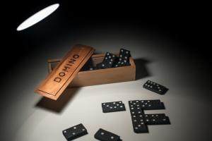 zwarte dominostenen in en naast een houten doos