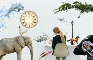 Meisje aan een bureau, omringd door en olifant, kip, dolfijn, helikopter, piraat