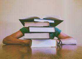 jongen achter stapel boeken aan tafel