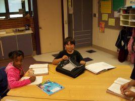 twee leerlingen aan grote bank in klaslokaal