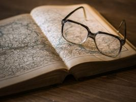 atlas die openligt met een bril erbij