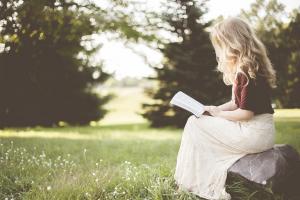 Vrouw leest een boek in de tuin