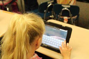 Een jong meisje werkt op haar tablet.