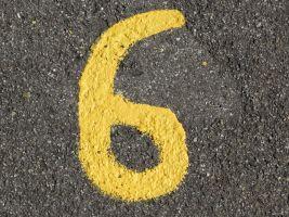 Cijfer zes met gele verf geschilderd op asfalt