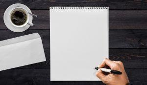 hand op een wit blad papier
