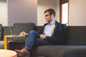Een man zit in zijn zetel en werkt op zijn laptop.