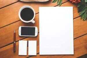 gsm, notitieblokjes met pen en een tas koffie
