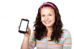 Een studente houdt haar smartphone vast.