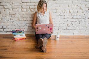 Meisje zit op de grond met laptop
