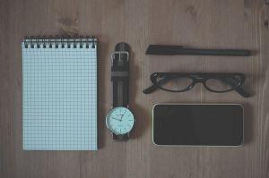Een tafel daarop ligt een notitieboekje, horloge, pen, bril en telefoon.