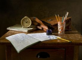 desk with exercise books, writing utensils, a clock ...