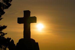 silhouet van een kruis met op de achtergrond een zon