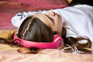 Meisje ligt op de grond met koptelefoon