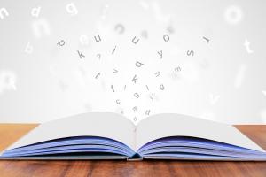opengeslagen boek waaruit letters opspringen
