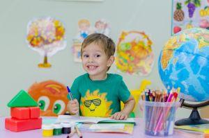 Lachend kind naast een wereldbol en ander schoolmateriaal.