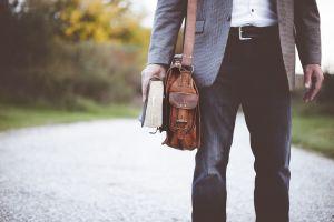 persoon met een boekentas en een boek vast