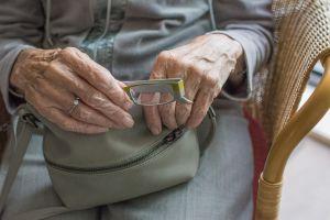Oudere dame haalt bril uit haar handtas