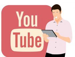 Een man houdt een tablet vast. Achter hem zie je het logo van YouTube.