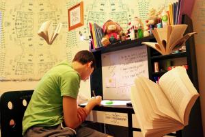 jongen studeert in zijn kamer