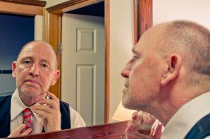 Man scheert zich in de spiegel