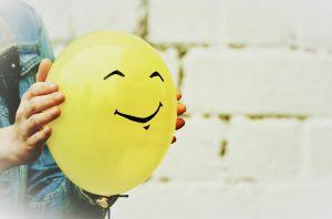 Iemand houdt een gele ballon vast met een gezicht erop getekend