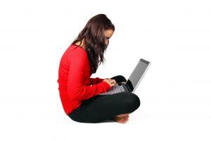 Meisje zit op de grond te werken met een laptop