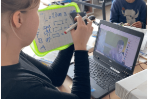 leerling aan lessenaar met laptop en whiteboard