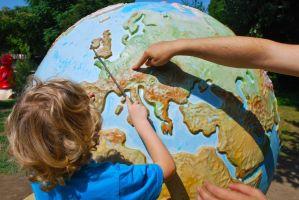 Kind wijst continent aan op wereldbol.