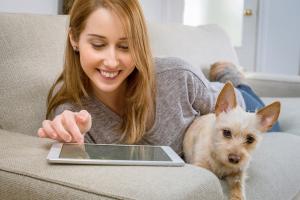Meisje werkt op tablet. Ze heeft een hondje vast.