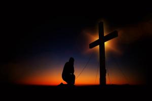 Schaduw van een persoon knielt voor een kruisbeeld